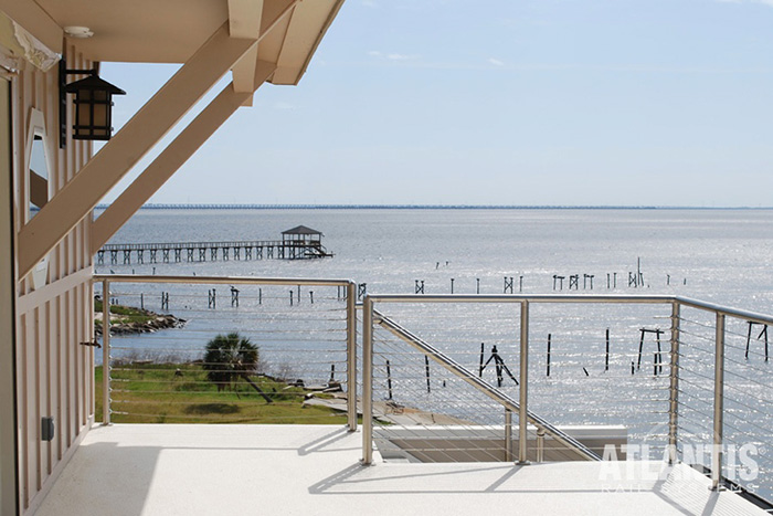 Home with clean cable railing around deck with a view of ocean and pier.